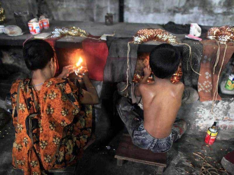 Hridoy, 7, (R) works in front of a small kiln at a glass bangle factory in Old Dhaka. According to the management of the factory, around 150 women and children work some 15 hours a day manufacturing glass bangles. Reuters photo/Andrew Biraj