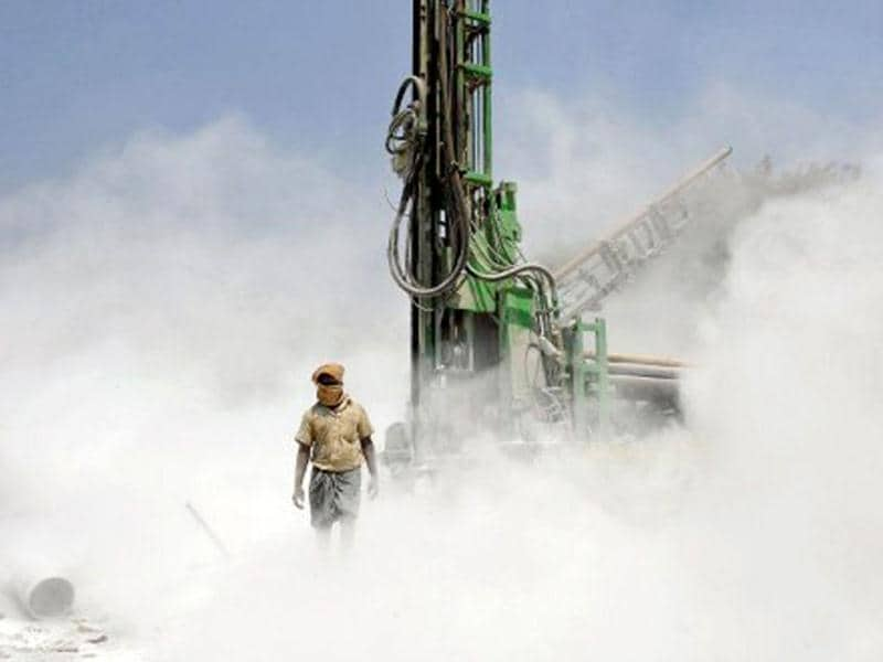 A worker walks out of dust emnating from a borewell rig drilling into the earth on the outskirts of Bangalore. India's six biggest cities - Mumbai, Delhi, Kolkata, Bangalore, Chennai and Hyderabad - are among those most affected by water shortages. According to UN, population growth and unsustainable consumption are driving Earth towards