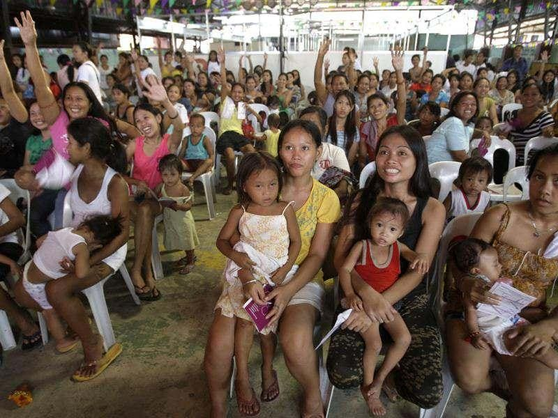 Filipino women and their children participate in a family planning fair to commemorate World Population Day in Manila, Philippines. Residents living in slum areas were given free family planning information, counseling and services. AP/Aaron Favila