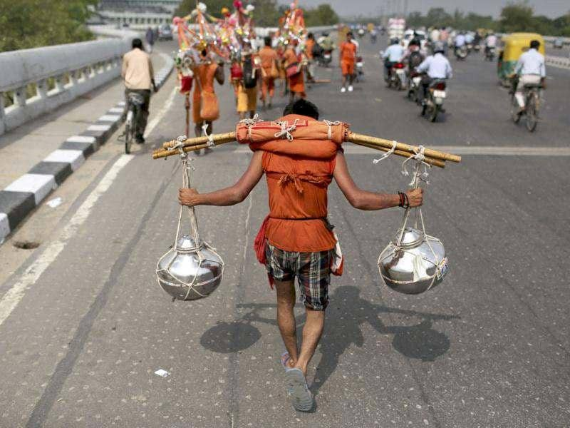 A Kanwaria, worshipper of God Shiva, struggles with carrying two canisters filled with water from the river Ganges during a pilgrimage in New Delhi. AP Photo/Kevin Frayer