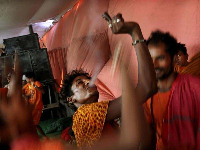 A Kanwaria, worshipper of God Shiva, smokes marijuana and dances to devotional songs in New Delhi. AP Photo/Kevin Frayer