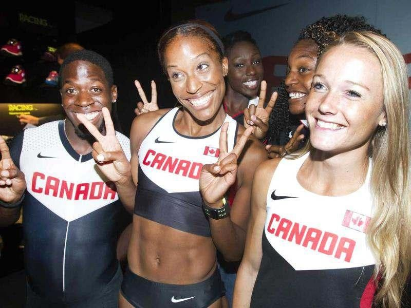Canadian Olympic athletes Phylicia George (C), Justyn Warner (L) and Sarah Wells (R) gesture at reporters along with other Olympic athletes at a press conference held by Nike and Athletics Canada to unveil Canadian Olympic team apparel in Toronto. (Reuters/Fred Thornhill)