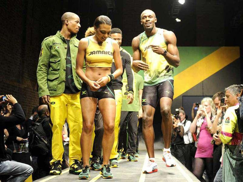 Jamaican sprinter Usain Bolt (R) models the Jamaican team's kit for the London 2012 Olympic Games, designed by Cedella Marley, at a fashion show in London. (Reuters/Paul Hackett)