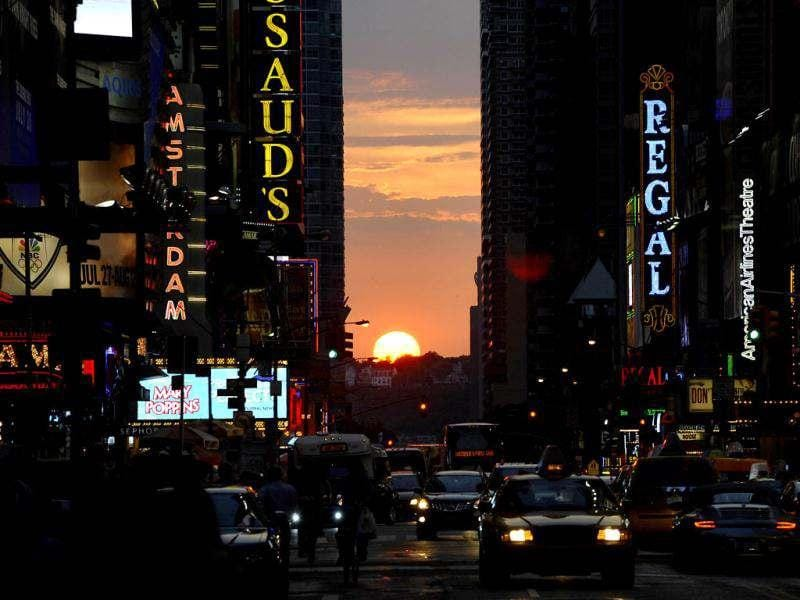 The sun sets as seen from 42nd street in New York City as Manhattanhenge, sometimes also referred to as Manhattan Solstice, the biannual natural event, when it is perfectly aligned with Manhattan's numbered streets. AFP PHOTO / TIMOTHY A. CLARY