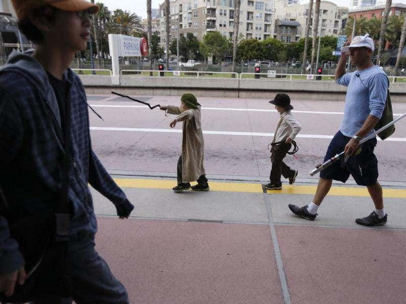 Brothers Devon and Trevor McPhillips walk with their father Ryan McPhillips as they arrive to Comic Con. AP/Gregory Bull