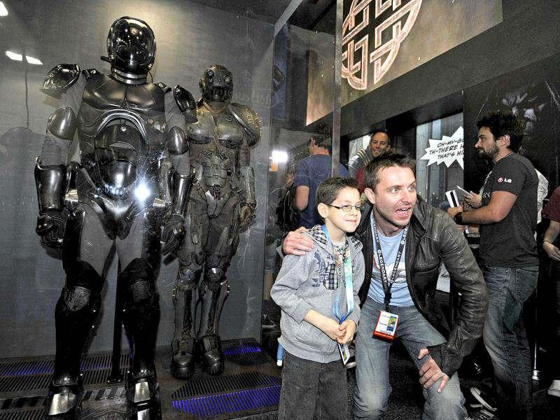 Christopher Hardwick poses with a fan next to costumes for the movie Pacific Rim on preview night at Comic Con at the San Diego Convention center in San Diego. AP/Denis Poroy