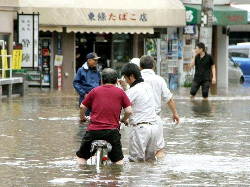 People wade through a flooded street caused by heavy rains in Kumamoto, southwestern Japan. Reuters/Kyodo
