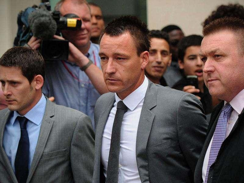 Chelsea and England footballer John Terry (C) leaves Westminster Magistrates court in London after he was found not guilty of racially abusing rival footballer Anton Ferdinand. AFP Photo/Carl Court