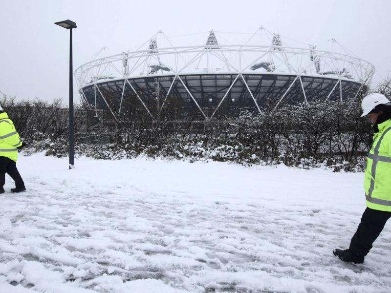 Security guards walk in the snow past the Olympic Stadium, which is being prepared for the London 2012 Olympic Games, in east London. Heavy snow fell in some areas of Britain overnight, causing road closures and flight cancellations, and the Met Office warned of icy conditions, local media reported. Reuters/Olivia Harris