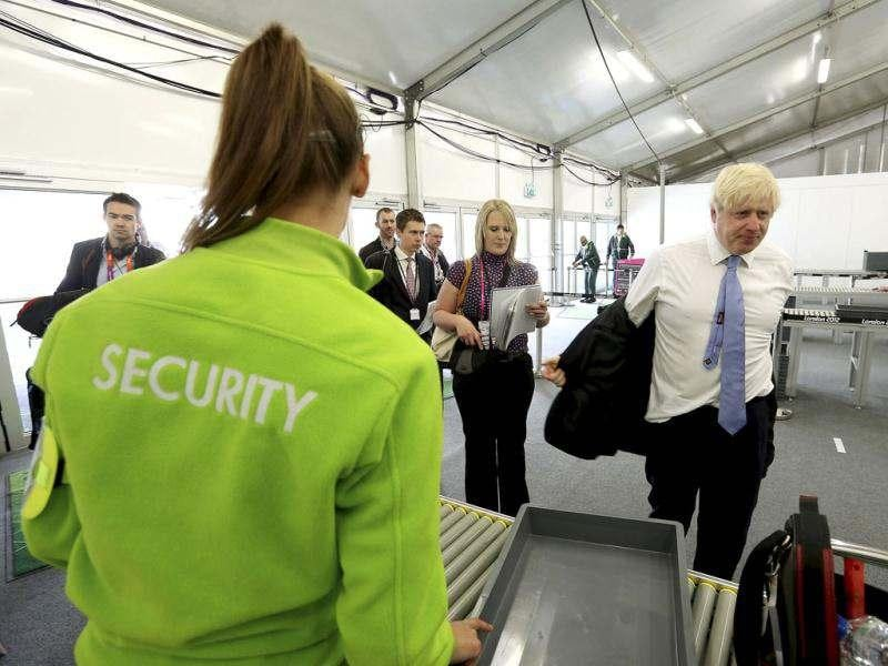 Mayor of London, Boris Johnson, removes his jacket as he passes through a security check during his visit to the 2012 Olympic Park in London. Reuters/Scott Heavey/Pool