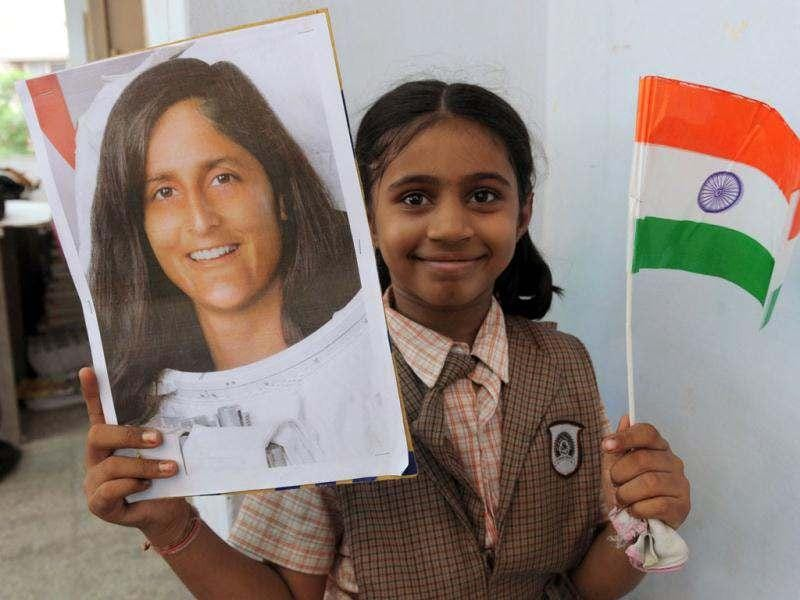 A schoolgirl poses with a portraits of US astronaut of Indian-Slovenian origin Sunita Williams, during a prayer gathering on the eve of her second scheduled journey to space, in Ahmedabad. (AFP photo/Sam Panthaky)