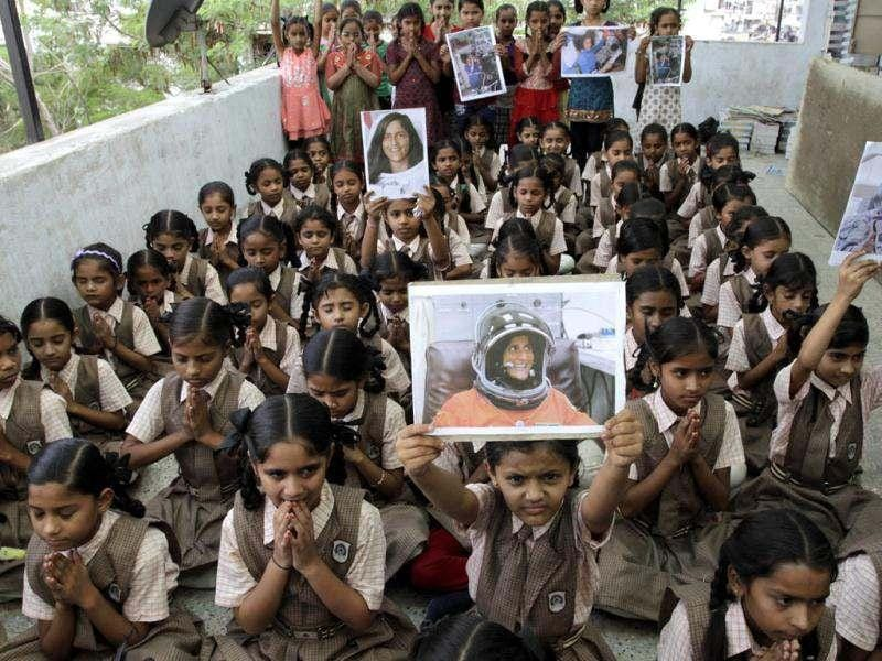 School children hold portraits of American astronaut of Indian origin Sunita Williams as they pray for successful journey to the International Space Station (ISS), in Ahmedabad. (AP Photo/Ajit Solanki)