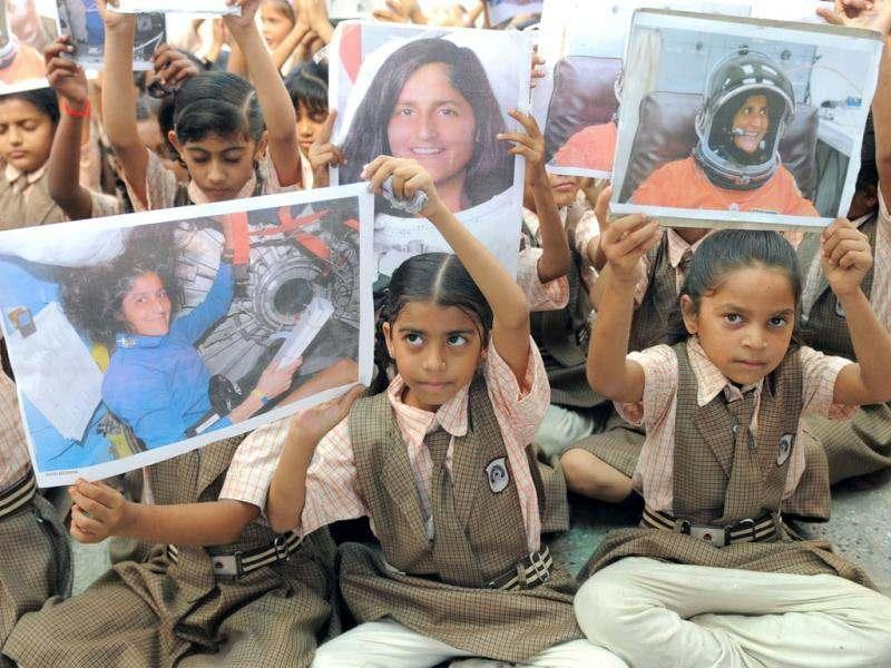 Schoolchildren pose with portraits of US astronaut of Indian-Slovenian origin Sunita Williams, during a prayer gathering on the eve of her second scheduled journey to space, in Ahmedabad. (AFP Photo/ Sam Panthaky)