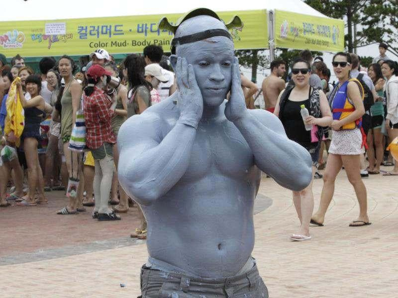 A tourist with his body painted with colored mud, strolls during the 15th annual mud festival on Daecheon Beach in Boryeong. (AP Photo/Ahn Young-joon)