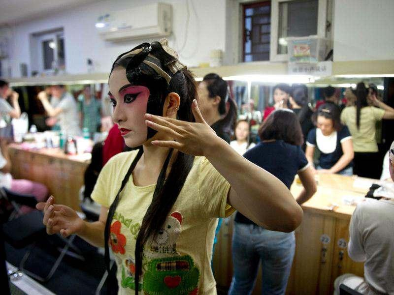 Performers preparing backstage prior to their show at the Temple Theatre of the Beijing Opera House in Beijing. Beijing's Temple Theatre performs titles by late 20th century opera icon Mei Lanfang such as 'Drunken Princess' and 'Sylph Scattering Flowers' in 100-minute shows for tourists and aficionados alike. AFP/Ed Jones