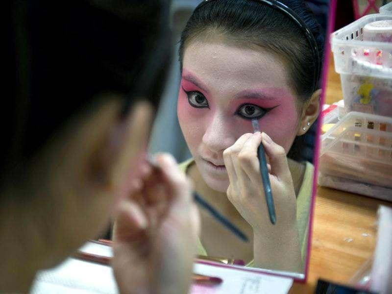 A performer applying makeup backstage prior to her appearing in a show at the Temple Theatre of the Beijing Opera House in Beijing. Beijing's Temple Theatre performs titles by late 20th century opera icon Mei Lanfang such as 'Drunken Princess' and 'Sylph Scattering Flowers' in 100-minute shows for tourists and aficionados alike. AFP/Ed Jones