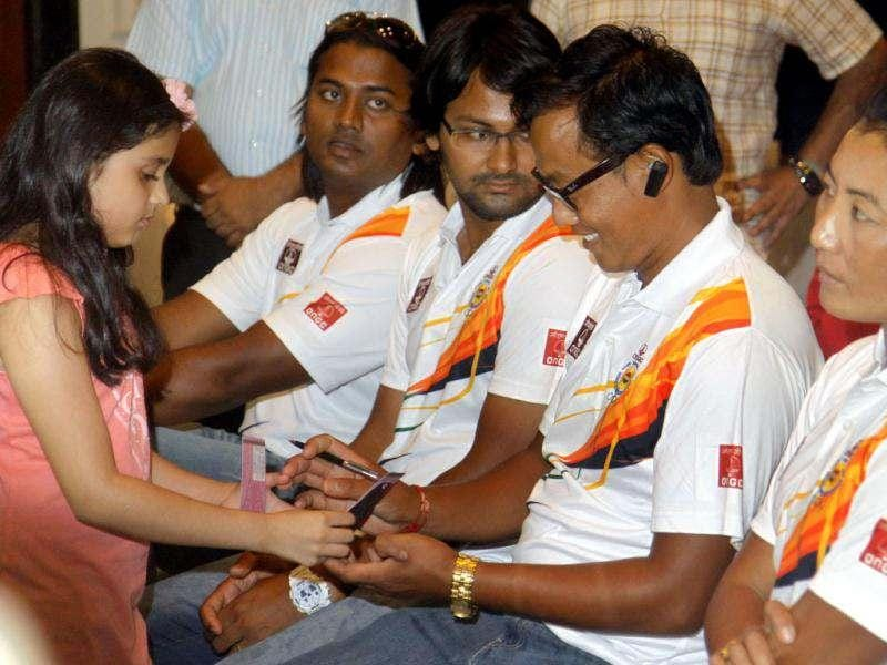 A young sports lover seek autograph from Olympic bound Indian Archers during ONGC organized Olympic players send of ceremony for London Olympic 2012 in New Delhi, India. (Hindustan Times Photo/Sonu Mehta)