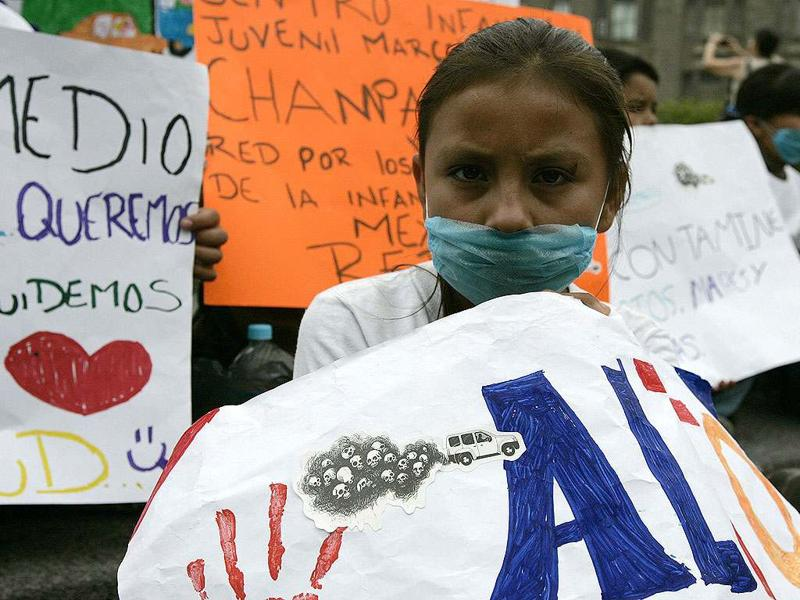 A child wearing a surgical mask holds up placard with a drawing ,as she takes part in a march aimed at pressuring local authorities to take stronger actions against air pollution in Guadalajara. The event was organized by