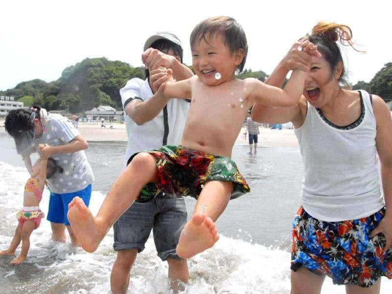 In this photo, a family plays on Nakoso beach in Iwaki, Fukushima prefecture, Japan. Fukushima prefecture (state) has opened its first beach to swimmers since last year's nuclear disaster after judging the water to be safe. AP Photo/Kyodo News