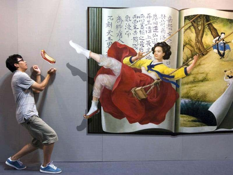 A man poses for a photograph near a 3D painting at the 2012 Magic Art Special Exhibition in Hangzhou, Zhejiang province. The event will run till August 6 in Hangzhou. Reuters/Stringer