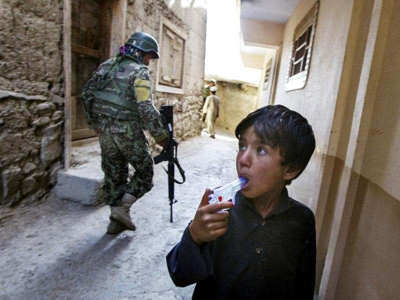 An Afghan boy drinks water from the barrel of a squirt gun as he watches Afghan National Army soldiers and paratroopers from Chosen Company of the 3rd Battalion (Airborne), 509th Infantry on a helicopter assault mission to improve their biological database, near the town of Ahmad Khel in Afghanistan's Paktiya Province. Reuters photo/Lucas Jackson