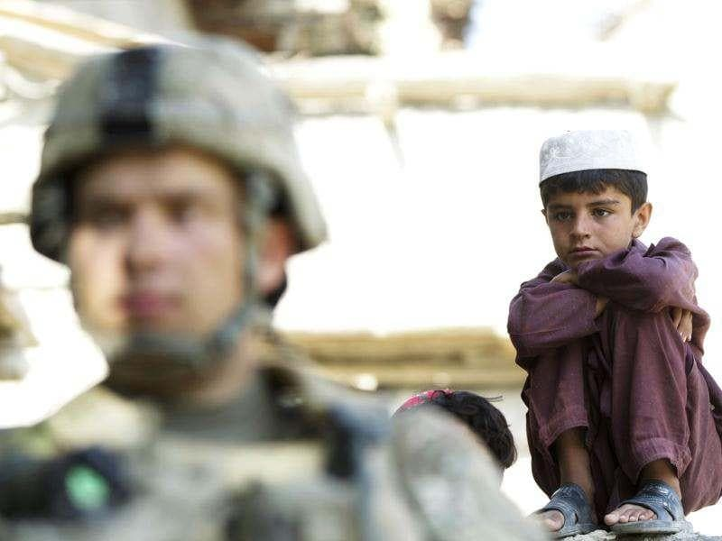 An Afghan boy watches a paratrooper from Chosen Company of the 3rd Battalion (Airborne), 509th Infantry provide security on a helicopter assault mission to improve their biological database of fighting aged males, near the town of Ahmad Khel in Afghanistan's Paktiya Province. Reuters photo/Lucas Jackson