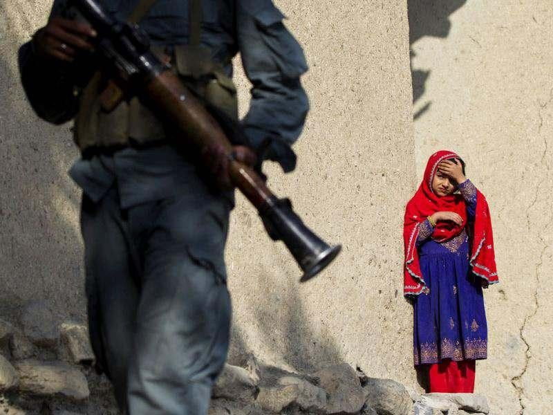 An Afghan girl watches as a member of the Afghan Uniformed Police walks past with paratroopers from Chosen Company of the 3rd Battalion (Airborne), 509th Infantry on a helicopter assault mission to improve their biological database, near the town of Ahmad Khel in Afghanistan's Paktiya Province. Reuters photo/Lucas Jackson