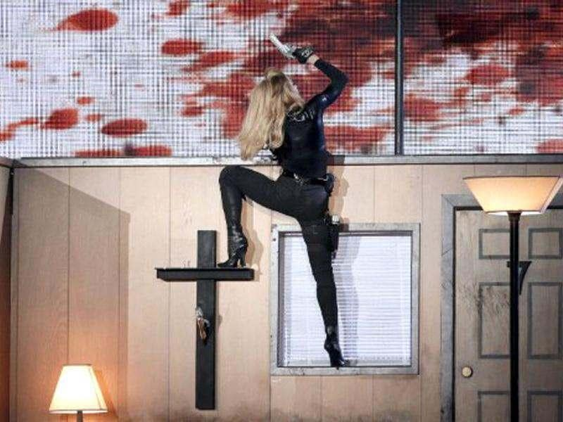 Does Madonna look victorious after climbing the cross during her MDNA world tour in France.