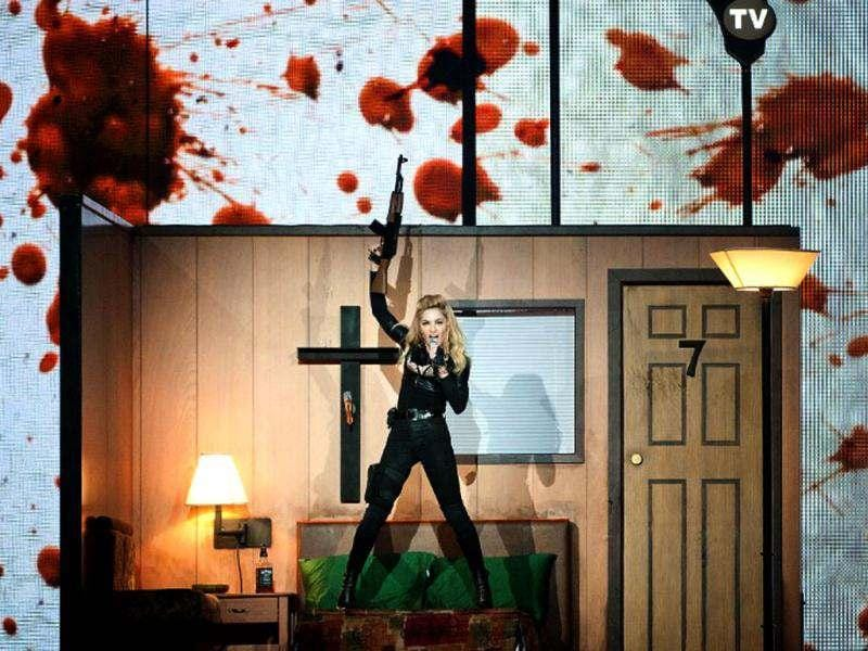 Madonna proudly posed with machine gun against a backdrop of a blood-splattered wall during her MDNA tour in Belgium.