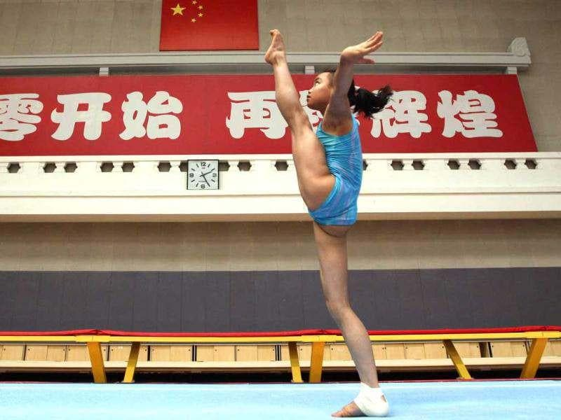 A gymnast from the Chinese national gymnastics team practices during a training session at General Administration of Sport of China, in Beijing. These young gymnasts are training for the Rio de Janeiro 2016 Olympic Games. The Chinese characters on the wall read,