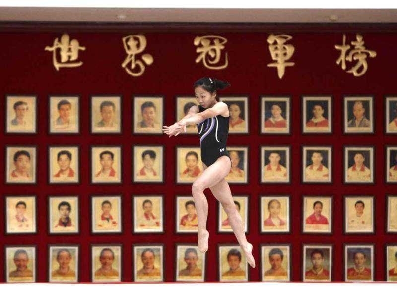 A gymnast from the Chinese national gymnastics team practices in front of portraits of Chinese Olympic and World Gymnastics champions during a training session at General Administration of Sport of China, in Beijing. These young gymnasts are training for the Rio de Janeiro 2016 Olympic Games. REUTERS/Jason Lee