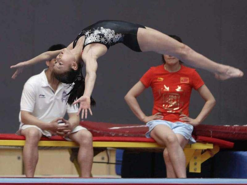 A gymnast from the Chinese national gymnastics team practices next to coaches during a training session at General Administration of Sport of China, in Beijing. These young gymnasts are training for the Rio de Janeiro 2016 Olympic Games. REUTERS/Jason Lee