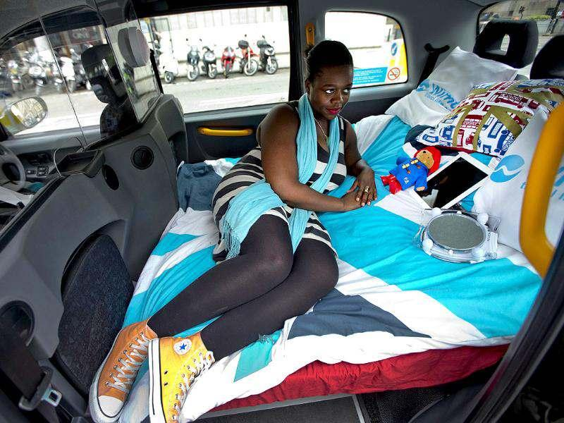 Jennifer Tetteh who works in public relations poses for photographs in the back of a parked London taxi that can be converted into a hotel room for people during the Olympics, in London. (AP Photo/Matt Dunham)