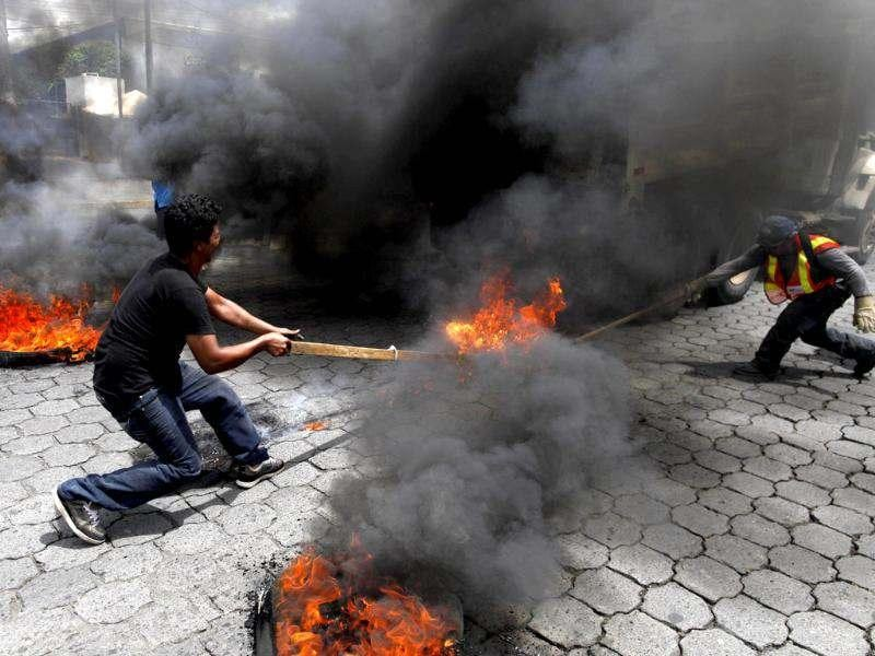 Members of Broad Opposition Front, FAO, civil organization, set on fire a vehicle belonging to Managua's town council during a protest in front of the Supreme Electoral Council, CSE, in Managua, Nicaragua. (AP Photo/Esteban Felix)