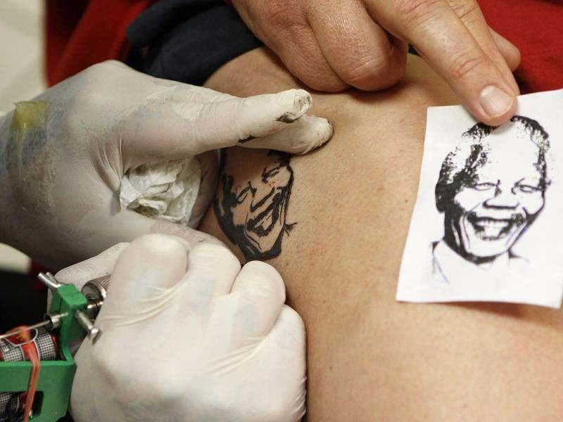 This photo shows a tattoo artist Charles Hearne create a tattoo portrait of former South African President Nelson Mandela on the upper leg of customer Hein van Tonder at a tattoo studio in Pretoria, South Africa. Hearne is attempting to have 67 customers tattooed to honour Mandela's 67 years in politics as the country celebrates Mandela's 94th birthday today. AP Photo/Denis Farrell