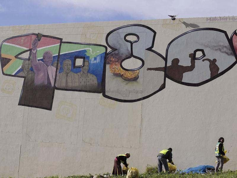 In this photo, workers clean the area around a mural depicting former South African President Nelson Mandela during iconic moments in the the 60's 70's 80's and 90's in Cape Town, South Africa. Mandela will celebrate his 94th birthday today. AP Photo/Schalk van Zuydam