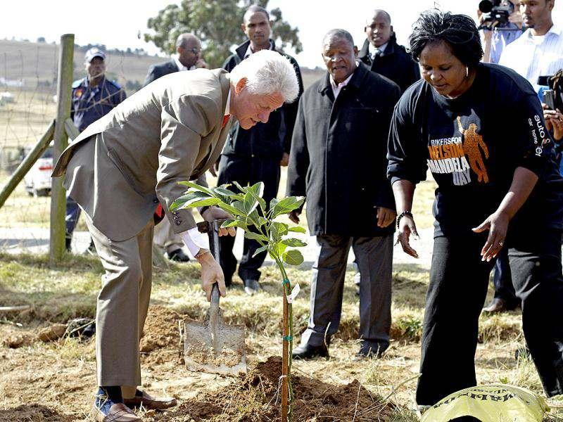 Former American President Bill Clinton, left, plants a tree to celebrate former South African president Nelson Mandela birthday in Qunu, South Africa. South African's will celebrate former president Nelson Mandela's birthday today. AP Photo/Schalk van Zuydam