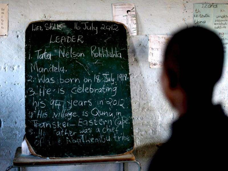School children read the history of former South African President Nelson Mandela written on a chalkboard, ahead of the opening of a container library by the Bill Clinton foundation in celebration of Mandela day, at a school in Qunu. Former US President Bill Clinton visited Mandela at his residence ahead of his 94th birthday celebrations. Reuters/Siphiwe Sibeko