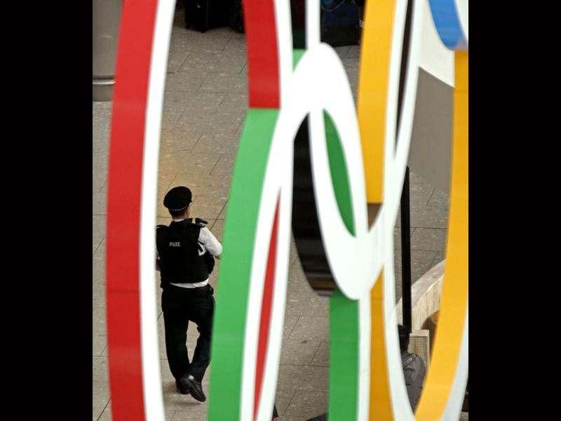 An airport police officer is framed by the Olympic Rings as he patrols an arrival terminal at Heathrow Airport. AP/Charlie Riedel