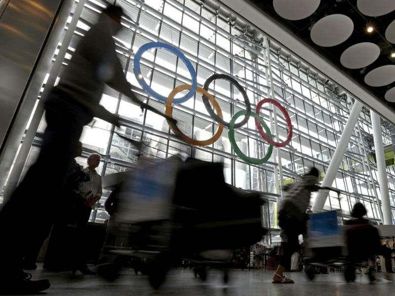 Travellers pass by the Olympic Rings hanging from an arrival terminal at Heathrow Airport. AP/Charlie Riedel
