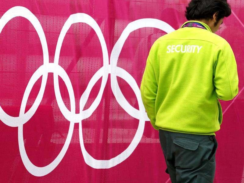 A security guard passes Olympic Rings signage at the London 2012 Olympic Park in Stratford, east London. Reuters/Luke MacGregor