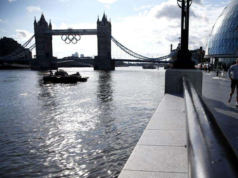 A jogger runs past Tower Bridge which displays the Olympic rings as London prepares for the 2012 Summer Olympics. AP/Jae Hong