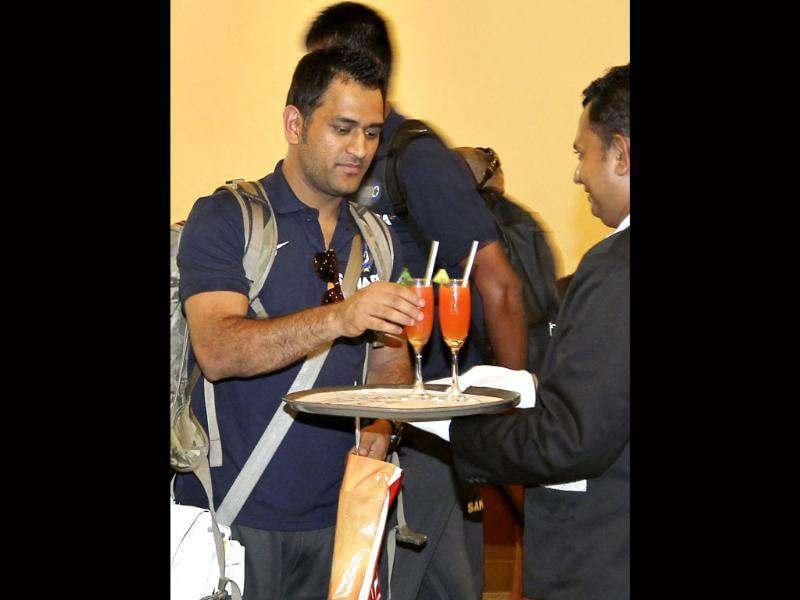 Mahendra Singh Dhoni receives a welcome drink upon the Indian cricket team's arrival in Colombo. AP/Gemunu Amarasinghe
