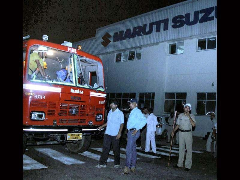 Policemen stand guard outside Maruti Suzuki's Manesar plant, damaged after clash between Workers and management employees. PTI