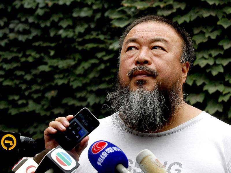 Dissident artist Ai Weiwei listens as his lawyer announces over a speakerphone the verdict of Ai's lawsuit against the Beijing tax authorities in Beijing. AP Photo/Ng Han Guan