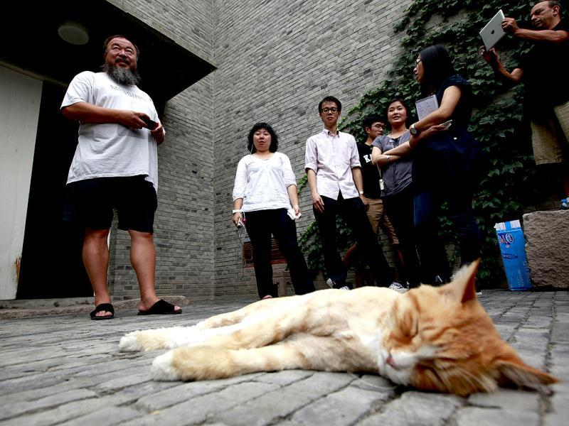 Dissident artist Ai Weiwei, left, waits with journalists at home for a verdict in his lawsuit against the Beijing tax authorities in Beijing. AP Photo/Ng Han Guan