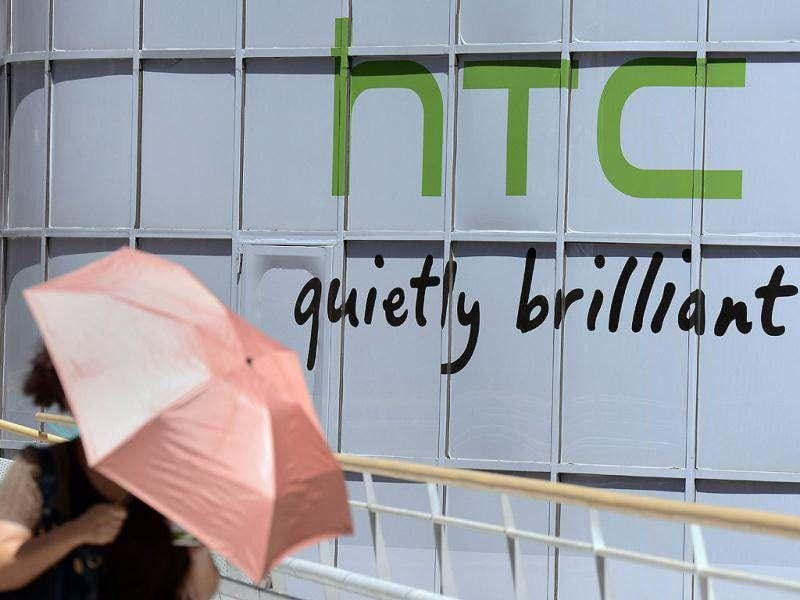 A woman walks past the logo for Taiwan's leading smartphone maker HTC in Taipei. AFP Photo/Sam Yeh