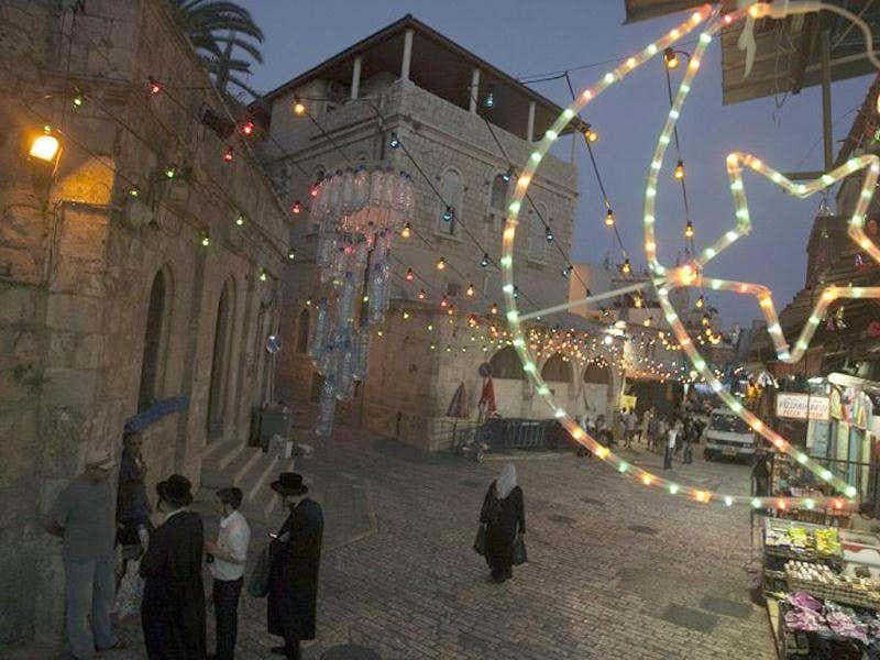 A Palestinian woman walks as Israeli Ultra-Orthodox Jewish men stand in a street decorated with Ramadan decorations, in the old city of Jerusalem to welcome the upcoming Muslim holy fasting month of Ramadan.(AFP Photo/Ahmad Gharabli)
