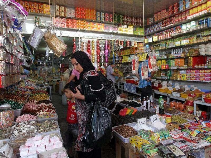 A woman buys sweets in preparation for the Muslim fasting month of Ramadan in Shorja Market in Baghdad. (AFP Photo/ Ahmad Al-Rubaye)