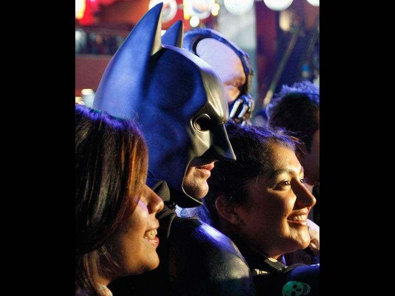 A man dressed as Batman poses with fans as they wait for a midnight premiere of